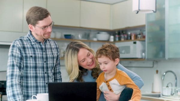 Family in kitchen with their laptop